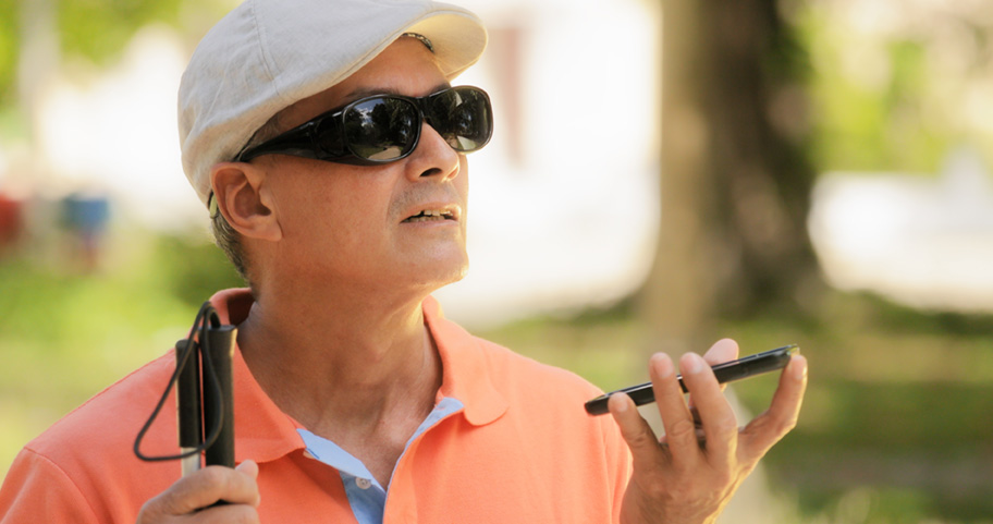 blind man wearing sunglasses and golfers hat caring white cane and  holding a cell phone